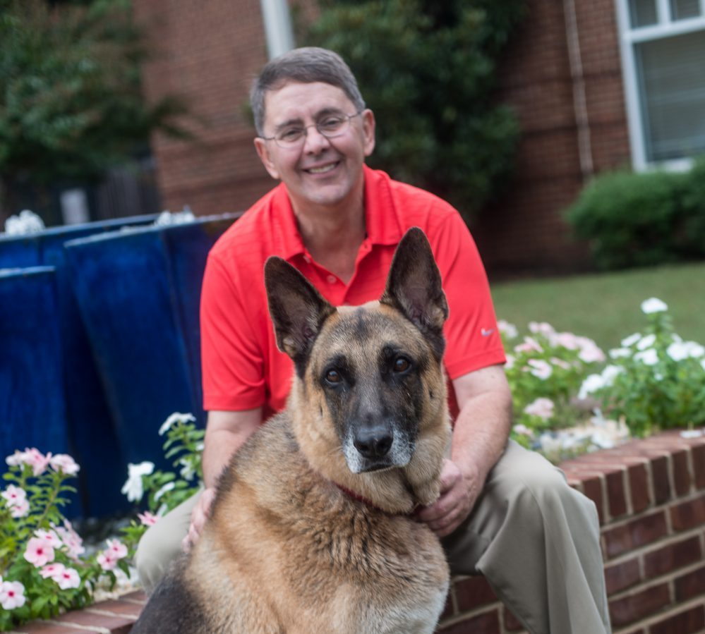 michael and sully german shephard sitting on brick wall