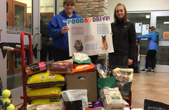 two young women with food donations for animals